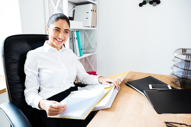 Веселая улыбающаяся деловая женщина читает документы, сидя за офисным столом