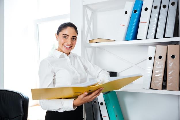 Веселая улыбающаяся деловая женщина стоит и держит желтую папку в офисе