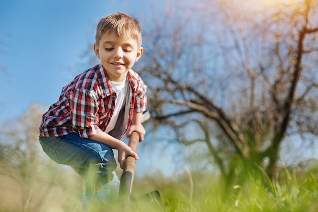 A cheerful smiling child scooping the soil with a spade in a family garden