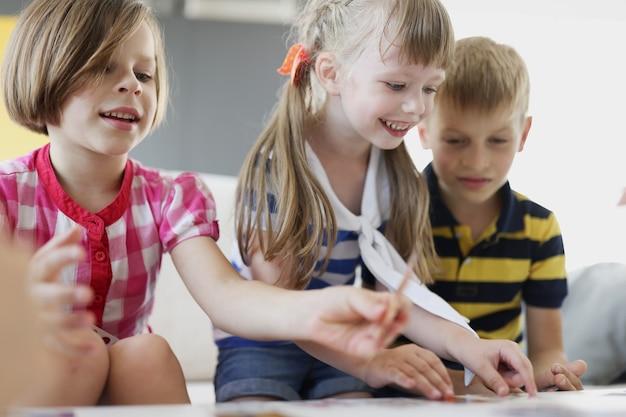 テーブルでボードゲームをしている陽気な笑顔の子供たち。子供の娯楽と趣味の概念