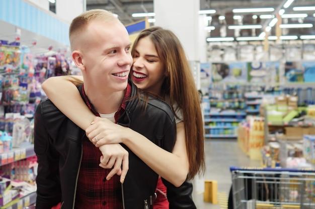 スーパーマーケットのハグ、コピースペースで陽気な笑顔のカップル