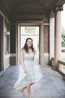 Cheerful smiling curly hair brunette in a light blue simple dress in a pavilion in a garden