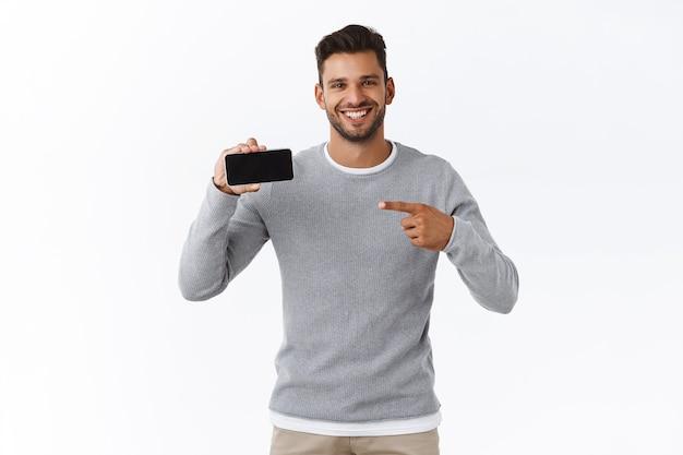쾌활하게 웃고 있는 귀여운 남자는 모바일 화면에서 조언 체크아웃 좋은 프로모션을 제공합니다