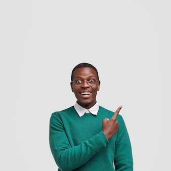 Cheerful smiling dark skinned male points with index finger upwards, glad to demonstrate free space for your promotion