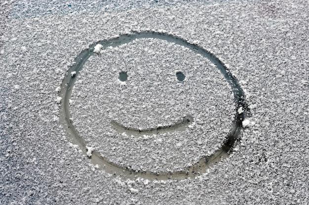 Веселое улыбающееся лицо нарисовано на заснеженном окне автомобиля.