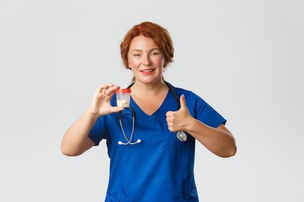 陽気な笑顔の女性医療従事者、ビタミンや薬の入った容器を見せているスクラブの医者は、承認で親指を立てて、丸薬を勧めます。