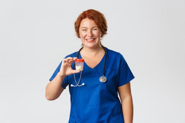 陽気な笑顔の女性医療従事者、ビタミンや薬の入った容器を見せているスクラブの医者は、灰色の背景に立っている錠剤をお勧めします。