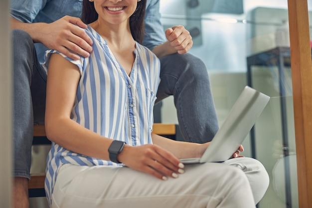 현대 집의 거실에 앉아 캐주얼 블라우스를 입고 밝은 웃는 여성