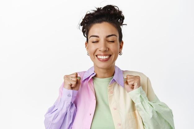Веселая улыбающаяся девушка, испытывающая радость и удовлетворение от победы, празднуя успех, достигая цели, прыгая от радости на белом