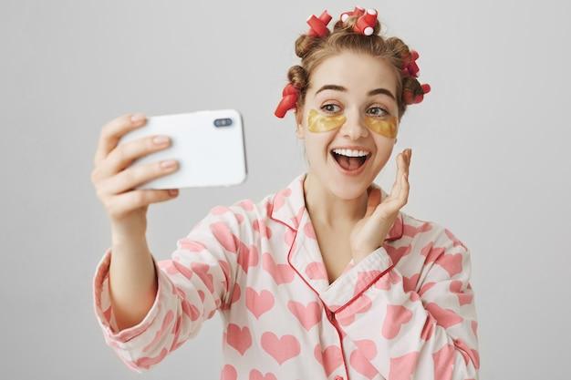 Ragazza sorridente allegra in bigodini e bende sugli occhi prendendo selfie indossando indumenti da notte