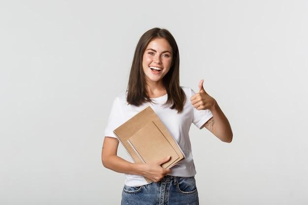 Веселая улыбающаяся девочка держит тетради и показывает палец вверх