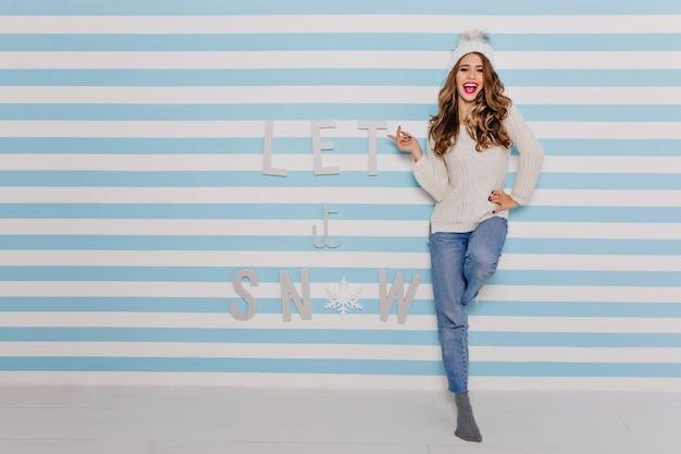 機嫌の良い陽気な笑顔の女の子は、白い縞模様の青い壁にコケティッシュにポーズをとっています。