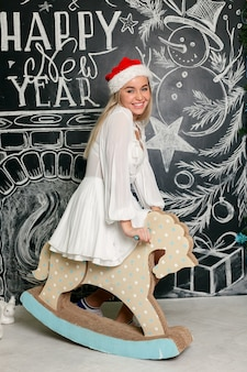 Cheerful smiling girl in santa claus cap riding a wooden horse with christmas writings on a chalkboard