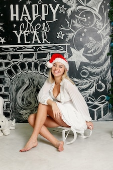 Cheerful smiling girl in santa claus cap with christmas writings on a chalkboard