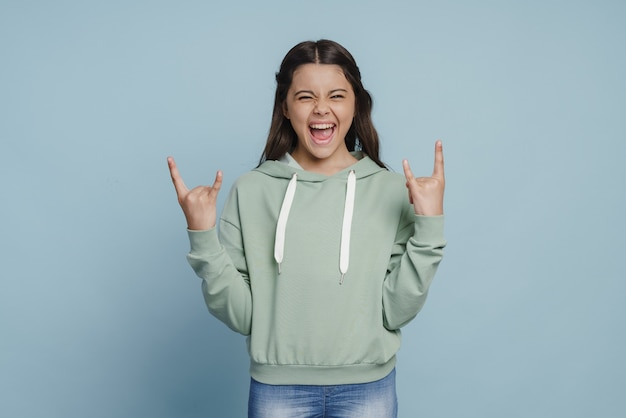 Веселая, улыбающаяся девушка показывает жест рок-н-ролла. милая маленькая девочка позирует на фоне синей стены