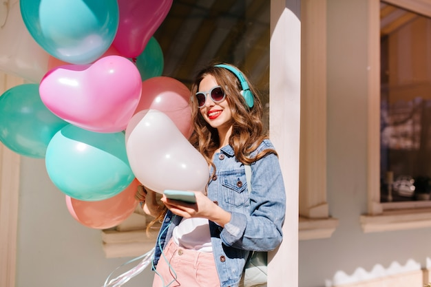 Cheerful smiling girl in stylish sunglasses going to event and listening favourite music in headphones. adorable young woman wearing retro denim jacket carrying colorful balloons to birthday party.