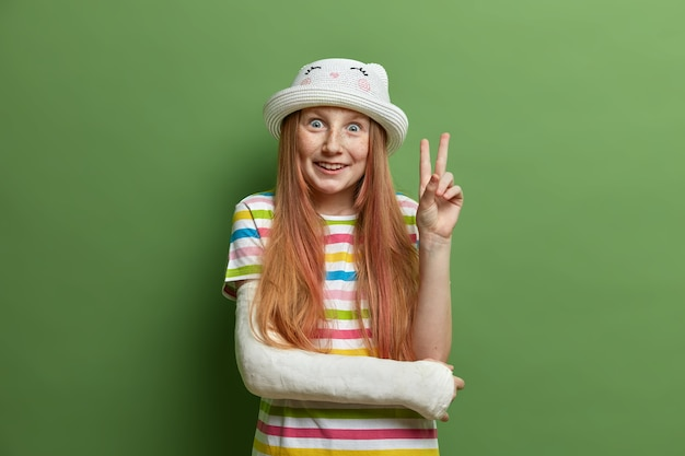 Веселая улыбающаяся девушка с радостным выражением лица делает знак победы или мира, носит шляпу и полосатую футболку, развлекается, сломанная рука в гипсовой повязке, изолированная на зеленой стене. дети, язык тела