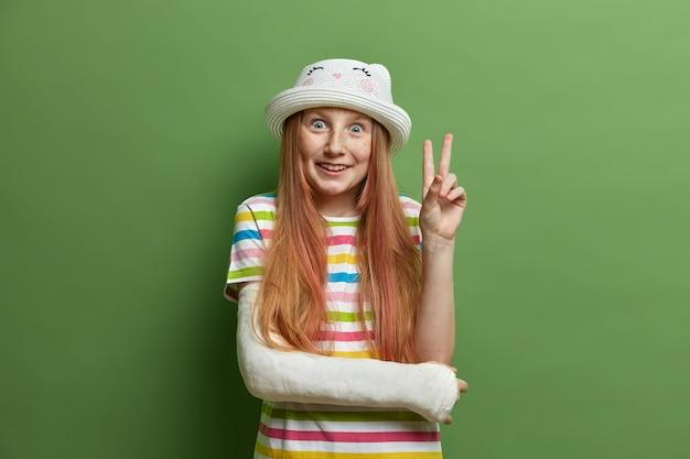 Ragazza sorridente allegra con espressione gioiosa, fa un gesto di vittoria o di pace, indossa cappello e maglietta a righe, si diverte, braccio rotto in calco in gesso, isolato sulla parete verde. bambini, linguaggio del corpo