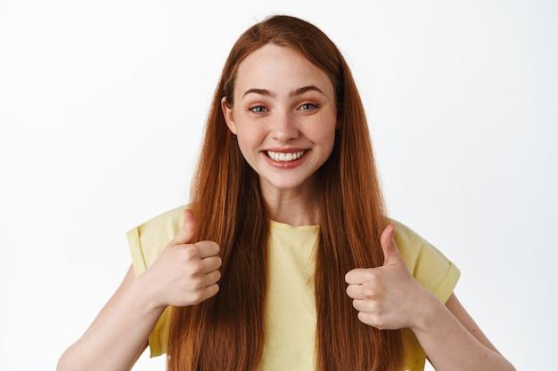 赤い髪の陽気な笑顔の女の子は、承認に親指を立てて、「はい」と言って、満足しているように見え、賞賛と褒め言葉の選択をし、孤立して立っています。