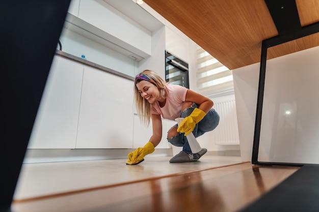 キッチンでしゃがみ、消毒剤で床を掃除し、汚れた場所をこすりながら、陽気な笑顔のゴージャスな整頓された主婦。