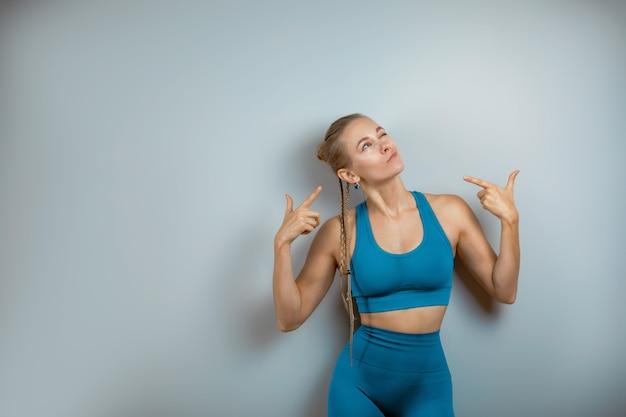 Веселая, улыбающаяся гимнастическая девушка показывает руками на месте текста, копией пространства