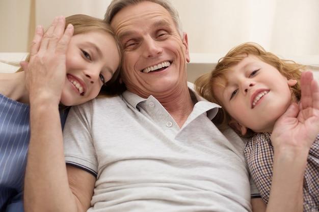 Веселый улыбающийся красивый мужчина делится счастливым моментом и выражает свою любовь, пока его дети навещают его на выходных