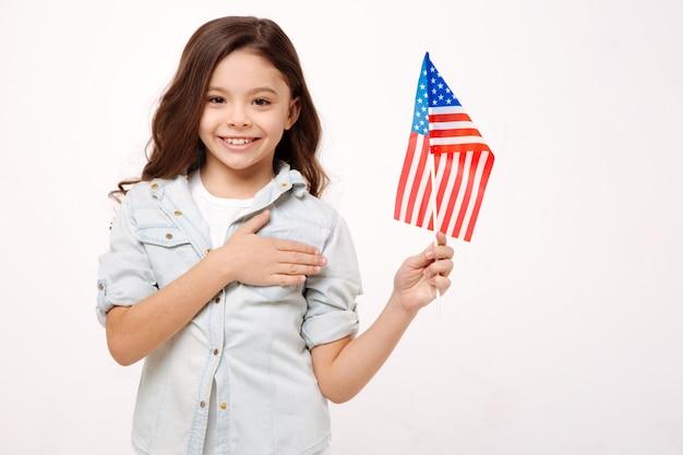 Веселая улыбающаяся счастливая девушка держит американский флаг и трогает ее грудь, выражая счастье и стоя у белой стены