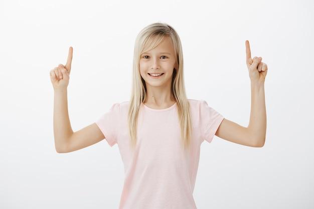 Allegro bambino sorridente che punta le dita verso l'alto