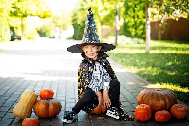 Веселый улыбающийся маленький мальчик в карнавальном костюме в шляпе сидит на тыквах в хэллоуин на открытом воздухе
