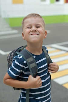 大きなバックパックと陽気な笑顔の小さな男の子