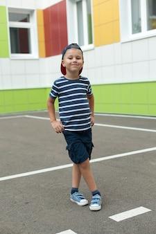 大きな青い帽子を持つ陽気な笑顔の小さな男の子