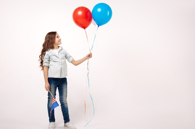 Веселая улыбающаяся маленькая девочка держит американский флаг и воздушные шары, выражая счастье и стоя изолированной в белой стене