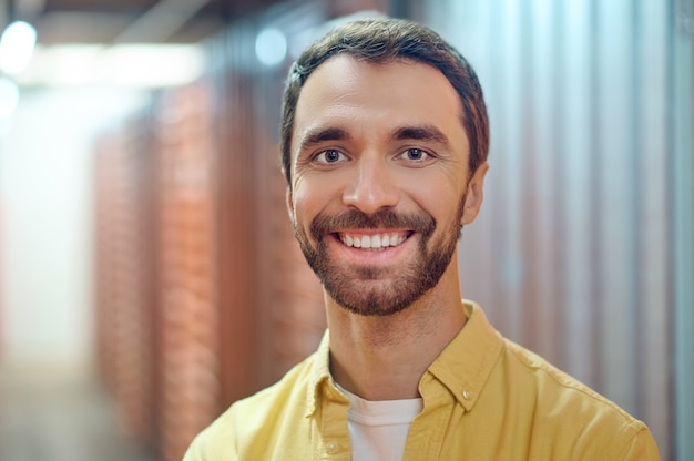 Веселый улыбающийся человек в подсобном помещении