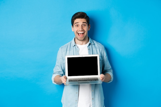 Cheerful smiling man making presentation, showing laptop screen and looking happy, standing over blue background.