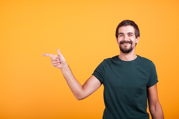 あなたの広告やプロモーションに利用できるコピースペースで彼の右を指している陽気な笑顔の男。スタジオのオレンジ色のbackgorundで隔離。