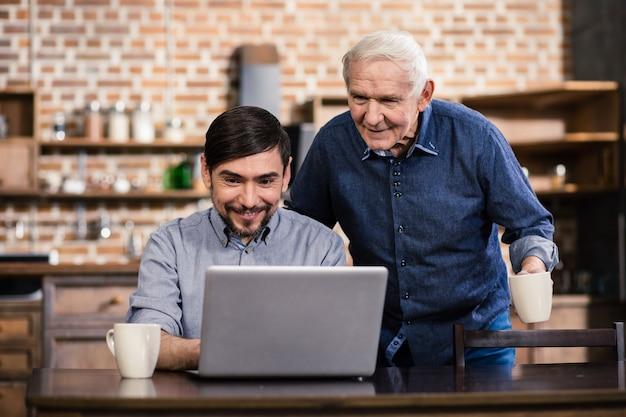 Веселый улыбающийся человек uisng ноутбук, пока его отец чувствует любопытство