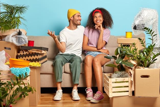 Allegra coppia sposata sorridente sogna un buon futuro nel loro nuovo appartamento