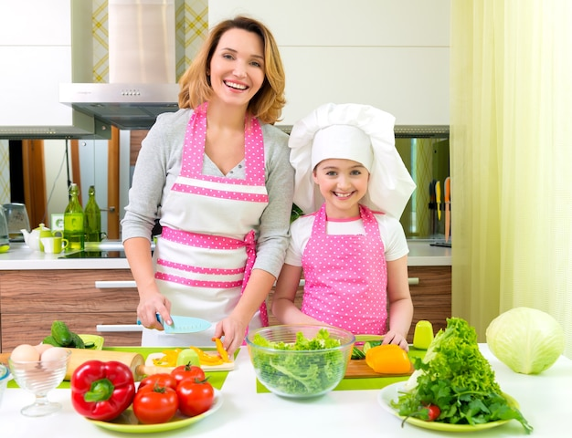 Cheerful smiling mother and daughter cooking a salad at the kitchen