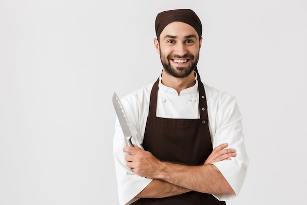 Cheerful smiling optimistic young sous-chef posing in uniform holding knife.