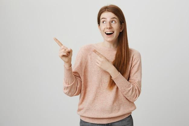 손가락 왼쪽 상단 모서리를 가리키는 밝은 웃는 빨간 머리 소녀