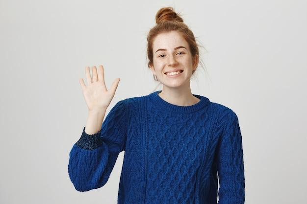 こんにちは、挨拶で手を振っている陽気な笑顔の赤毛の女の子