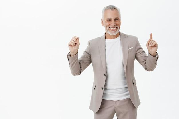 Allegro sorridente imprenditore senior che punta le dita verso l'alto