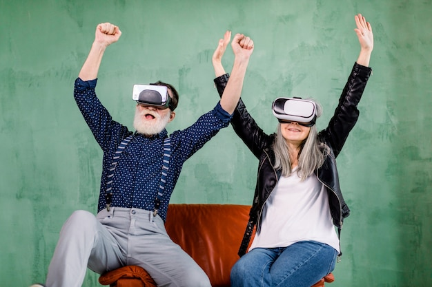 Cheerful smiling senior couple in stylish trendy clothes, sitting on red soft chair and enjoying video games or 3d film using virtual reality goggles, holding their arms up