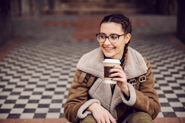 Веселая улыбающаяся девочка-подросток сидит на земле перед старым зданием, ждет друзей и пьет свежий кофе из одноразовой чашки.