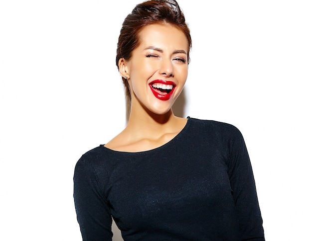 Cheerful smiling winking fashion woman going crazy in casual black clothes with red lips on white wall