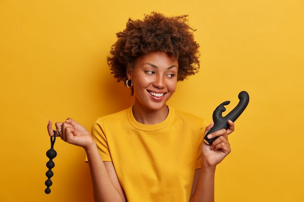 Cheerful smiling woman glad to return from sex shop, holds anal beads provide stimulation through movement in anus, vibrator to reach climax, being in good mood, cannot wait until masturbation