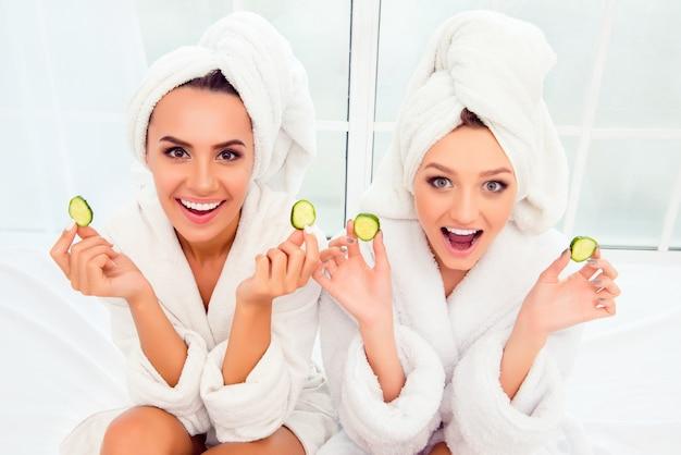 きゅうりのスライスを保持している彼らの頭にバスローブとタオルで陽気な笑顔の女性
