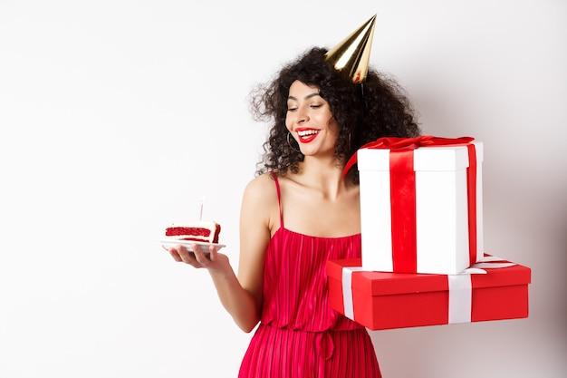 赤いドレスとパーティーコーンで陽気な笑顔の女性、誕生日ケーキを幸せそうに見て、贈り物を持って、白い背景の上に立っています。コピースペース