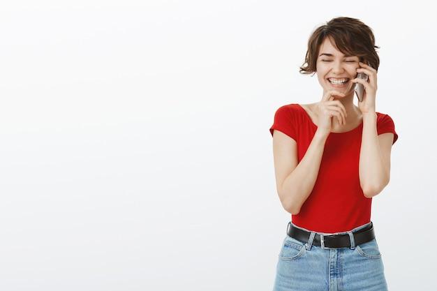 笑って、幸せな携帯電話で話している陽気な笑顔の女性