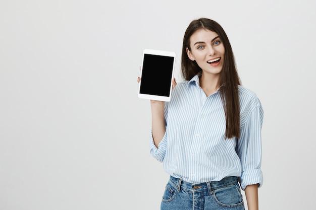 Donna sorridente allegra che mostra lo schermo della compressa digitale